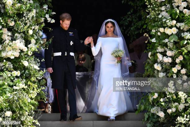 TOPSHOT Britain's Prince Harry Duke of Sussex and his wife Meghan Duchess of Sussex walk down the west steps of St George's Chapel Windsor Castle in...