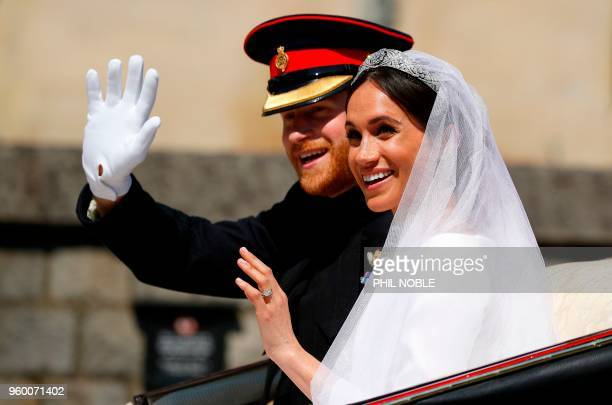 TOPSHOT Britain's Prince Harry Duke of Sussex and his wife Meghan Duchess of Sussex wave from the Ascot Landau Carriage during their carriage...
