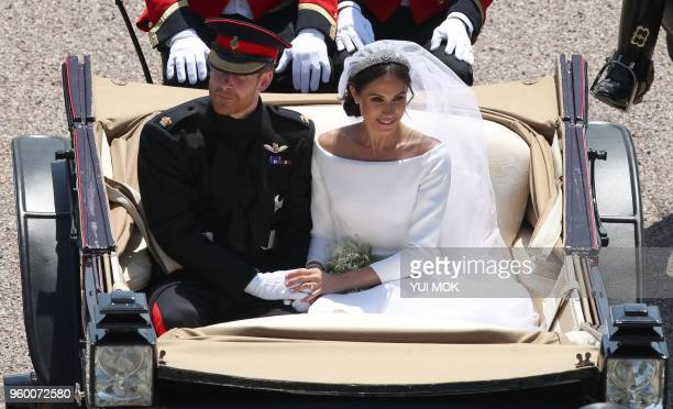 Britain's Prince Harry Duke of Sussex and his wife Meghan Duchess of Sussex ride in the Ascot Landau Carriage as they pass through the Cambridge Gate...