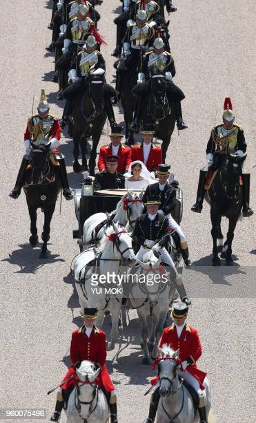 Britain's Prince Harry, Duke of Sussex and his wife Meghan, Duchess of Sussex, are escorted by members of the Household Cavalry Mounted Regiment as...