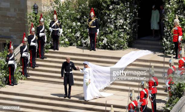 Britain's Prince Harry, Duke of Sussex and his wife Meghan, Duchess of Sussex emerge from the West Door of St George's Chapel, Windsor Castle, in...