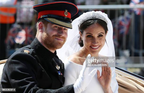 Britain's Prince Harry, Duke of Sussex and his wife Meghan, Duchess of Sussex wave from the Ascot Landau Carriage during their carriage procession on...