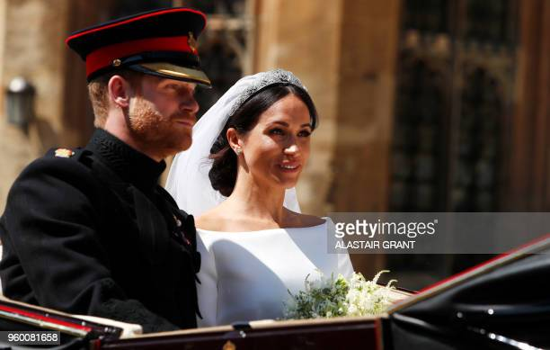 TOPSHOT Britain's Prince Harry Duke of Sussex and his wife Meghan Duchess of Sussex ride in the Ascot Landau Carriage at the start of their...