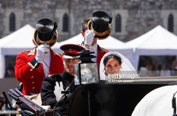 Britain's Prince Harry Duke of Sussex and his wife Meghan Duchess of Sussex ride in the Ascot Landau Carriage at the start of their procession after...