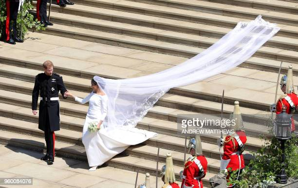 Britain's Prince Harry Duke of Sussex and his wife Meghan Duchess of Sussex walk down the west steps of St George's Chapel Windsor Castle in Windsor...