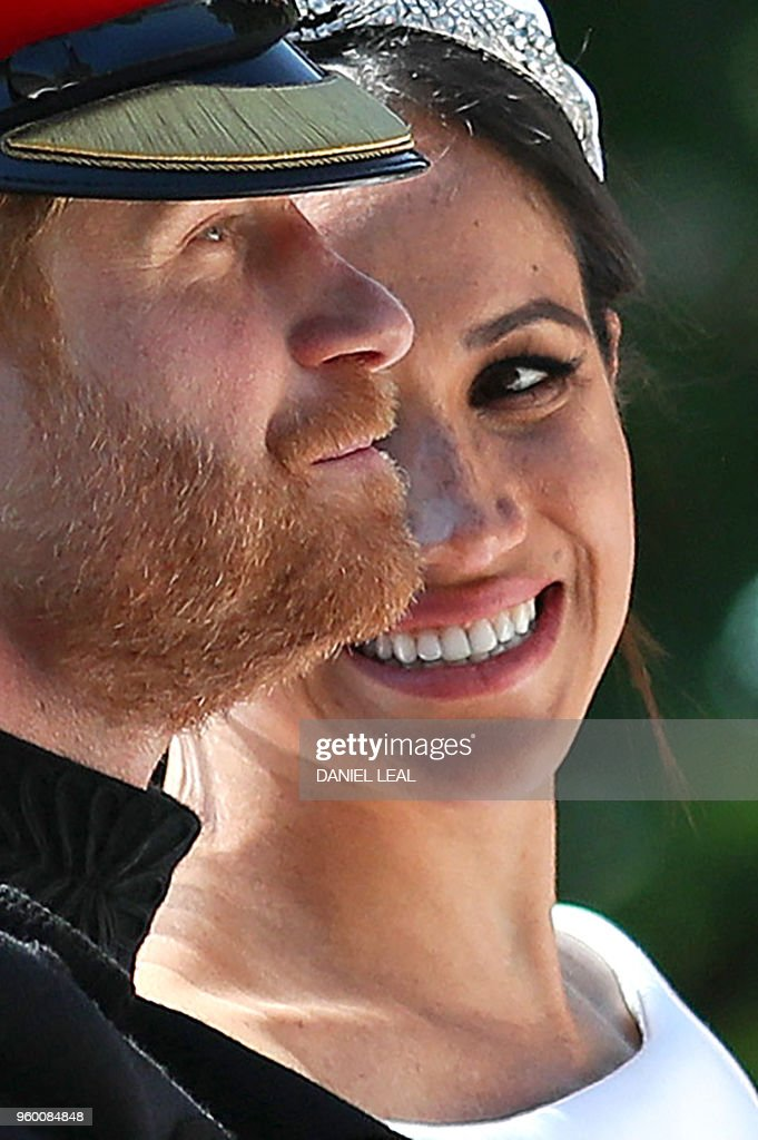 TOPSHOT - Britain's Prince Harry, Duke of Sussex and his wife Meghan, Duchess of Sussex travel in the Ascot Landau Carriage during their carriage procession on the Long Walk as they head back towards Windsor Castle in Windsor, on May 19, 2018 after their wedding ceremony.