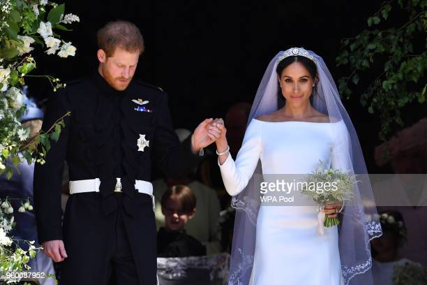 Britain's Prince Harry Duke of Sussex and his wife Meghan Duchess of Sussex leave from the West Door of St George's Chapel Windsor Castle in Windsor...