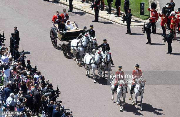 Britain's Prince Harry Duke of Sussex and his wife Meghan Duchess of Sussex begin their carriage procession in the The Ascot Landau carriage pulled...