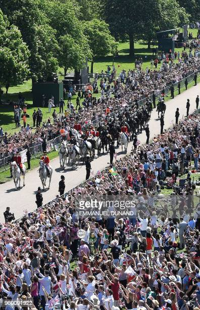 Britain's Prince Harry Duke of Sussex and his wife Meghan Duchess of Sussex wave from the Ascot Landau Carriage during their carriage procession on...