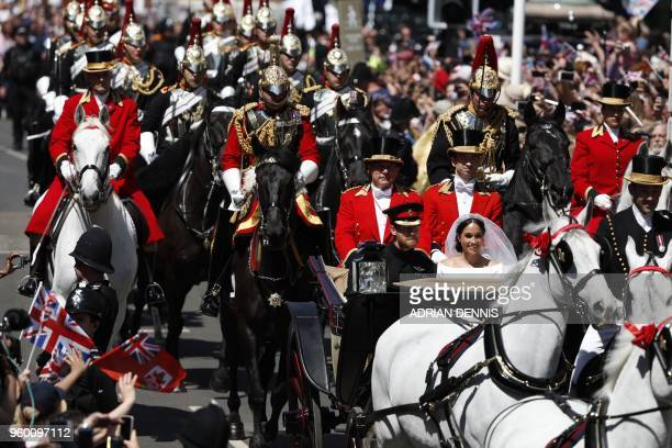 Britain's Prince Harry Duke of Sussex and his wife Meghan Duchess of Sussex travel in the Ascot Landau Carriage during their carriage procession on...