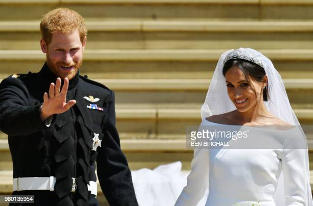 Britain's Prince Harry Duke of Sussex and his wife Meghan Duchess of Sussex emerge from the West Door of St George's Chapel Windsor Castle in Windsor...