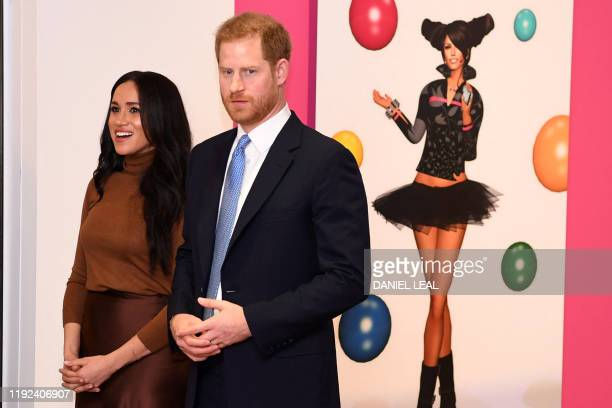 Britain's Prince Harry Duke of Sussex and Meghan Duchess of Sussex react as they view a special exhibition of art by Indigenous Canadian artist...