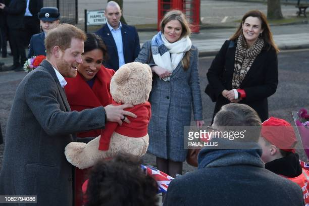 Britain's Prince Harry Duke of Sussex and Meghan Duchess of Sussex look at teddy bear as they greet wellwishers during their visit Birkenhead...