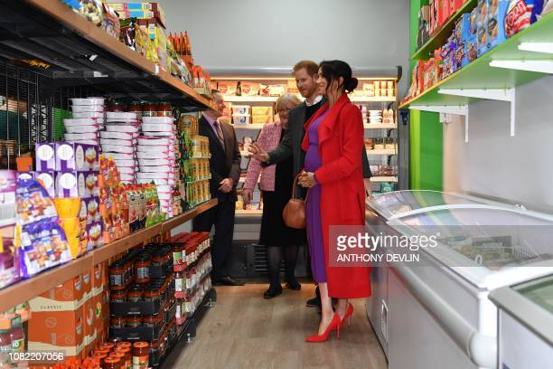 Britain's Prince Harry Duke of Sussex and Meghan Duchess of Sussex view products displayed for sale as they officially open 'Number 7' a 'Feeding...