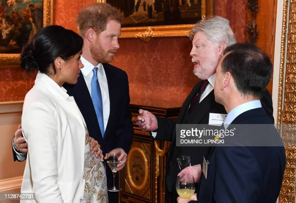 Britain's Prince Harry Duke of Sussex and Meghan Duchess of Sussex talk with British army veteran and charity campaigner Simon Weston and Britain's...