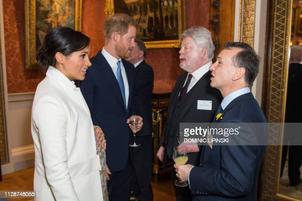 Britain's Prince Harry, Duke of Sussex and Meghan, Duchess of Sussex , talk with British army veteran and charity campaigner Simon Weston and...