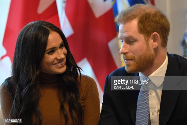 Britain's Prince Harry Duke of Sussex and Meghan Duchess of Sussex gesture during their visit to Canada House in thanks for the warm Canadian...