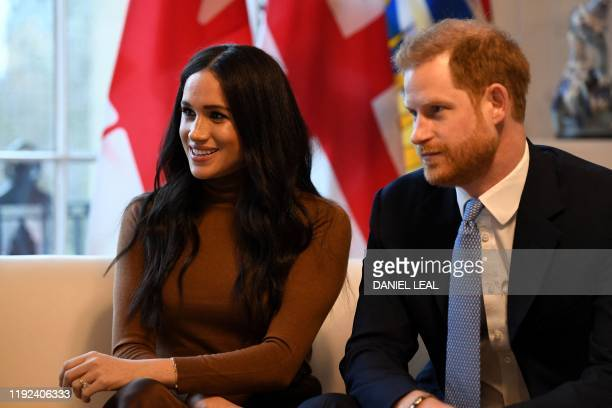Britain's Prince Harry, Duke of Sussex and Meghan, Duchess of Sussex gesture during their visit to Canada House in thanks for the warm Canadian...