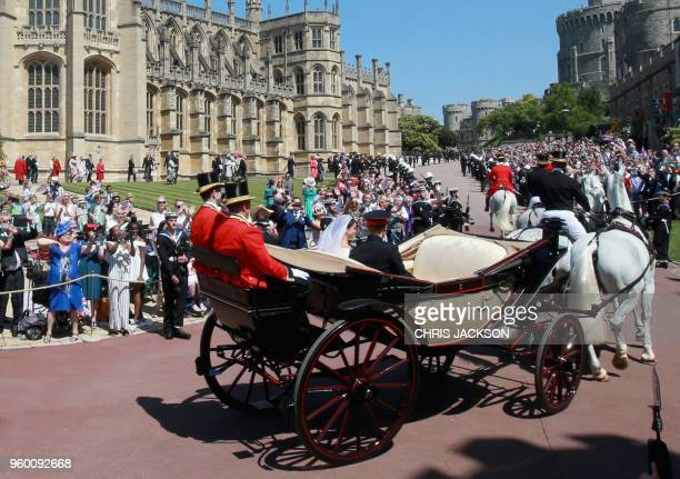 Britain's Prince Harry Duke of Sussex and Meghan Duchess of Sussex begin their carriage procession in the Ascot Landau Carriage after their wedding...