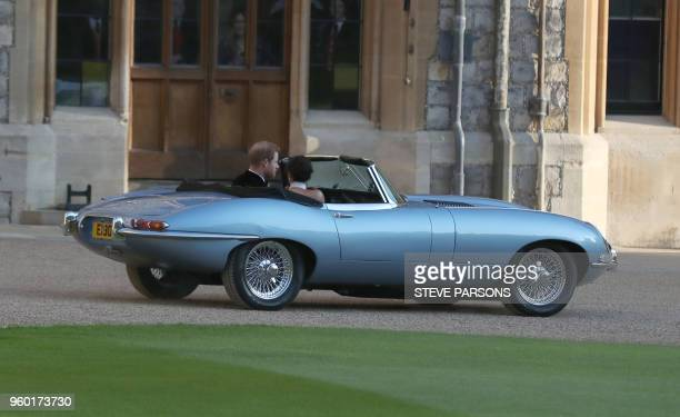 Britain's Prince Harry Duke of Sussex and Meghan Markle Duchess of Sussex leave Windsor Castle in Windsor on May 19 2018 in an EType Jaguar after...