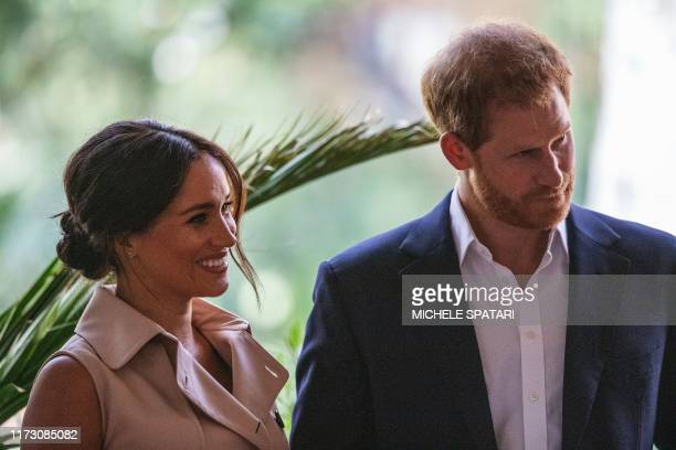 Britain's Prince Harry Duke of Sussex and Meghan the Duchess of Sussex stand on the stage at the British High Commissioner residency in Johannesburg...