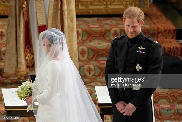 Britain's Prince Harry Duke of Sussex and US actress Meghan Markle stand at the altar in St George's Chapel Windsor Castle in Windsor on May 19 2018...