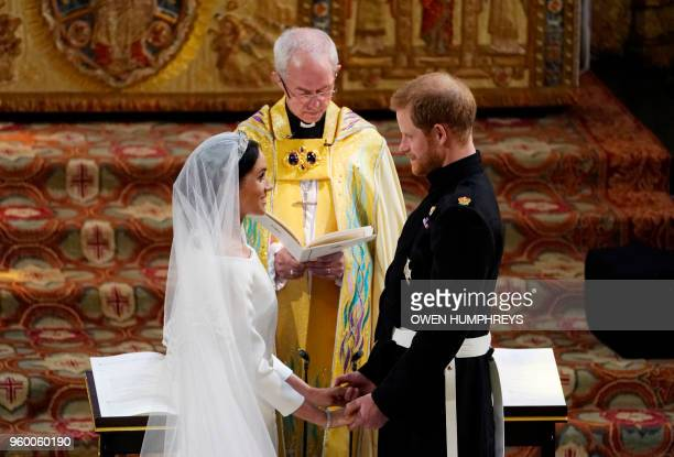 TOPSHOT Britain's Prince Harry Duke of Sussex and US actress Meghan Markle stand facing each other handinhand before Archbishop of Canterbury Justin...