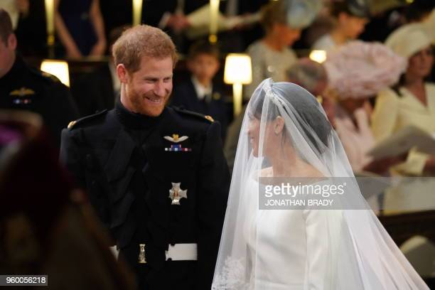 TOPSHOT Britain's Prince Harry Duke of Sussex and US fiancee of Britain's Prince Harry Meghan Markle arrive at the High Altar for their wedding...