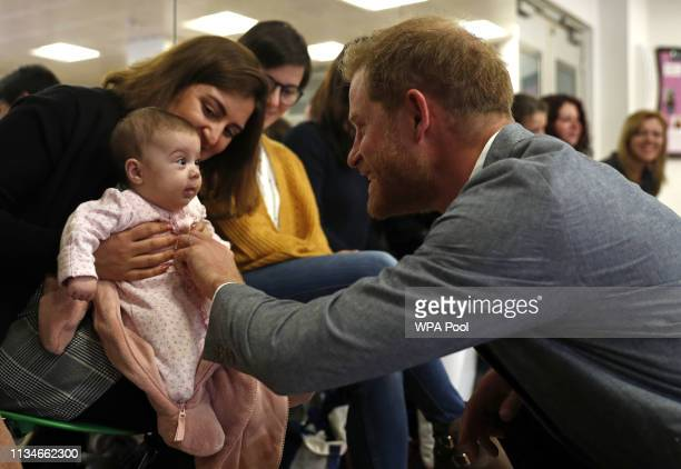 Britain's Prince Harry Duke of Sussex chats with 3 months old baby Naz and mother Maria Ahmad as they watch a ballet class for 4 to 6 year olds...