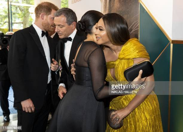 Britain's Prince Harry, Duke of Sussex chats with Disney CEO Robert Iger as Britain's Meghan, Duchess of Sussex embraces US singer-songwriter Beyoncé...