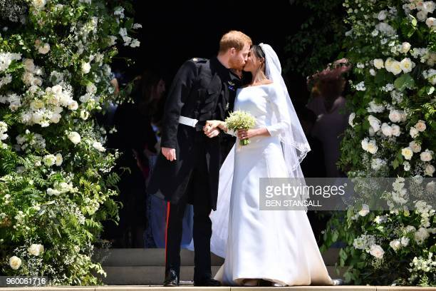 TOPSHOT Britain's Prince Harry Duke of Sussex kisses his wife Meghan Duchess of Sussex as they leave from the West Door of St George's Chapel Windsor...