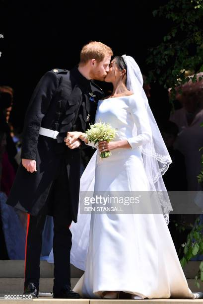 Britain's Prince Harry, Duke of Sussex kisses his wife Meghan, Duchess of Sussex as they leave from the West Door of St George's Chapel, Windsor...