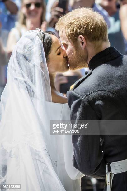 Britain's Prince Harry Duke of Sussex kisses his wife Meghan Duchess of Sussex as they leave from the West Door of St George's Chapel Windsor Castle...