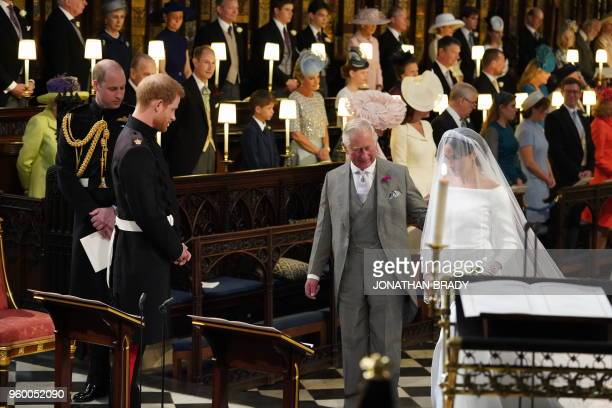 TOPSHOT Britain's Prince Harry Duke of Sussex looks at his bride Meghan Markle as she arrives accompanied by the Britain's Prince Charles Prince of...