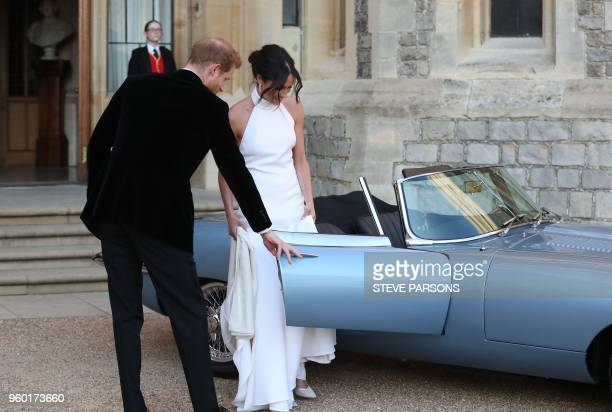 Britain's Prince Harry Duke of Sussex opens the passenger door of an EType Jaguar car for his wife Meghan Markle Duchess of Sussex as they leave...