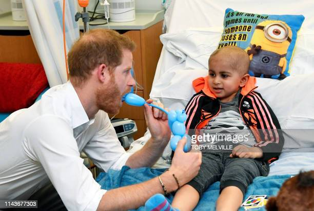 TOPSHOT Britain's Prince Harry Duke of Sussex plays with a patient as he visits the Oxford Children's Hospital in Oxford southern England on May 14...