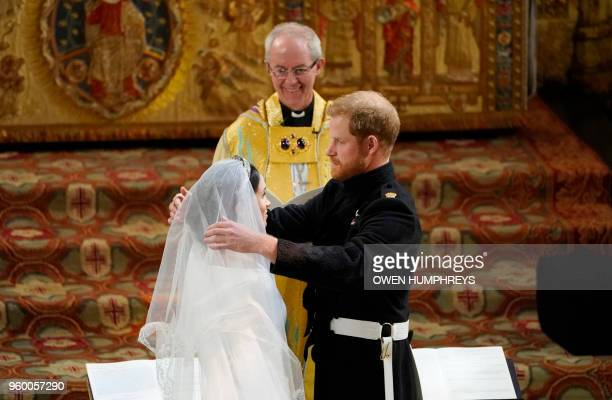 TOPSHOT Britain's Prince Harry Duke of Sussex removes the veil of US actress Meghan Markle as they stand at the altar together before Archbishop of...