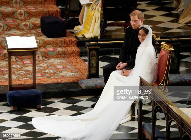 Britain's Prince Harry, Duke of Sussex sits with US actress Meghan Markle during the reading in St George's Chapel, Windsor Castle, in Windsor, on...