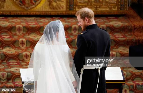 Britain's Prince Harry Duke of Sussex stands with US actress Meghan Markle at the altar in St George's Chapel Windsor Castle in Windsor on May 19...