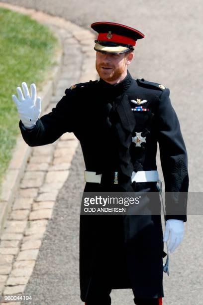 Britain's Prince Harry Duke of Sussex waves as he arrives at St George's Chapel Windsor Castle in Windsor on May 19 2018 for his wedding ceremony to...