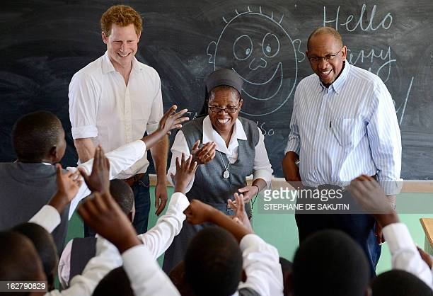 Britain's Prince Harry flanked by Sister Victoria Mota and Prince Seeiso, the younger brother of King Letsie of Lesotho, interacts with pupils at the...
