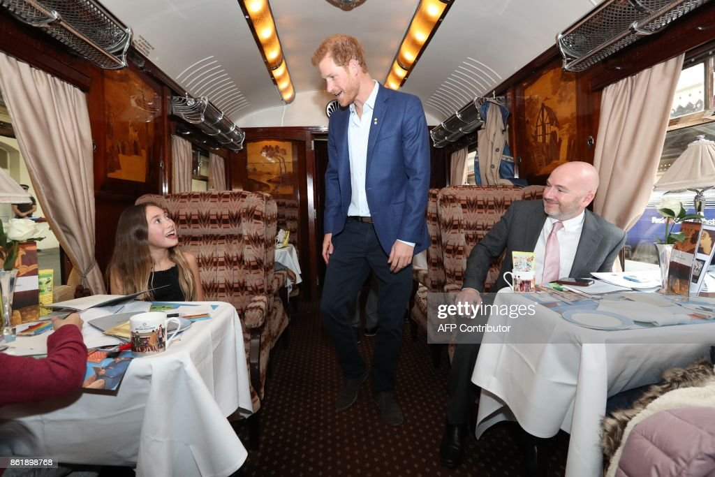Britain's Prince Harry (C), greets children supported by charities in the The Charities Forum aboard Belmond British Pullman train during an event at Paddington train station in London on October 16, 2017. The Duke and Duchess of Cambridge and Prince Harry joined children helped by the charities they support on board Belmond British Pullman train at Paddington Station. The event was hosted by STUDIOCANAL, with support from BAFTA through its BAFTA Kids programme, and before embarking Their Royal Highnesses met the cast and crew from the forthcoming film Paddington 2. / AFP PHOTO / POOL / Jonathan Brady