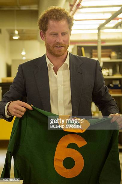 Britain's Prince Harry holds up the 1995 Rugby World Cup jersey gifted from South African rugby player Francois Pienaard to Nelson Mandela at the...