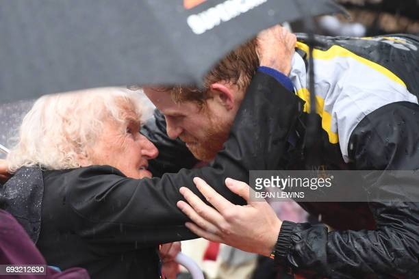 Britain's Prince Harry hugs Daphne Dunne during a walk around The Rocks in Sydney on June 7 2017 Prince Harry on June 7 paid tribute to victims of...