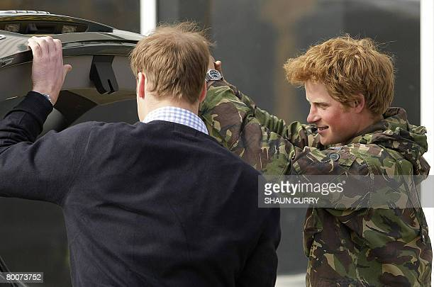 Britains Prince Harry is helped with his luggage by his Brother Prince William upon his arrival at RAF Brize Norton in Oxforshire March 1 after a...