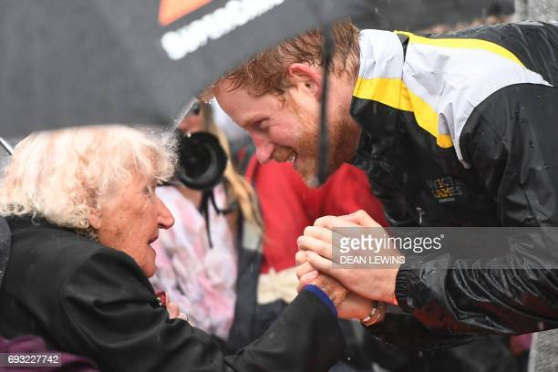 Britain's Prince Harry meets with Daphne Dunne at The Rocks in Sydney on June 7 2017 Prince Harry on June 7 paid tribute to victims of the London...