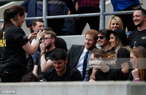 Britain's Prince Harry poses for a picture with competitors from the 2014 and 2016 Invictus Games in the crowd as he watches the annual Army Navy...