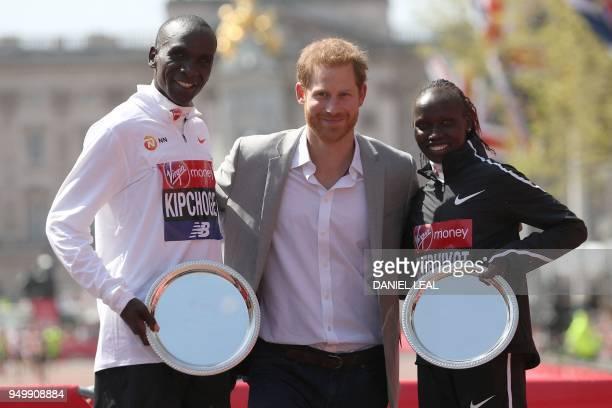 Britain's Prince Harry poses with elite men's race winner Kenya's Eliud Kipchoge and elite women's race winner Kenya's Vivian Cheruiyot during the...