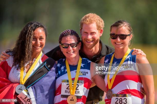 Britain's Prince Harry poses with IT1/IT2/IT3 100 meter medalists silver medalists Sabrina Daulaus of France Gold Medalist Sarah Rudder of the United...