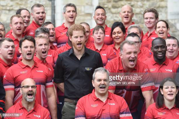 Britain's Prince Harry poses with members of the team who will represent the United Kingdom at the Invictus games at the Tower of London in central...